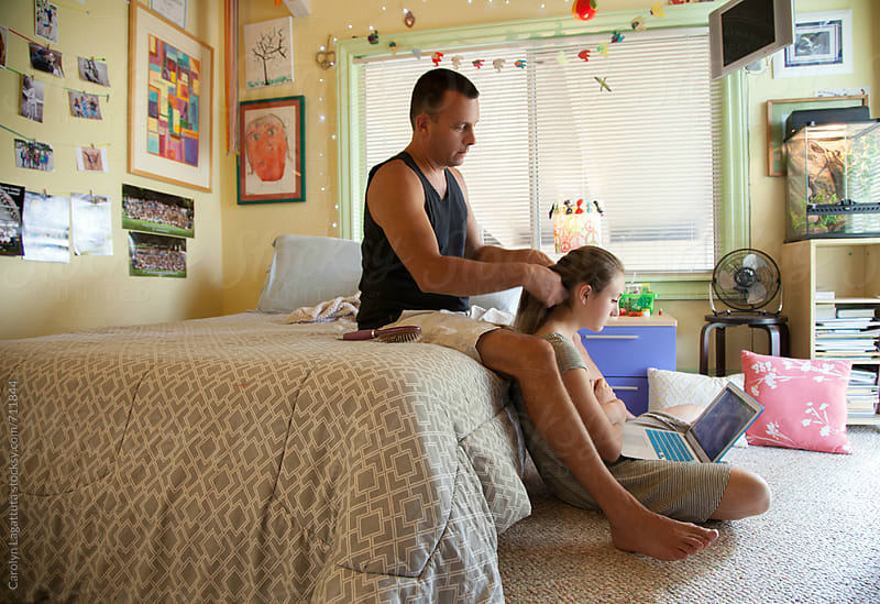 Father french braiding his teenage daughter's hair in her bedroom while she watches the laptop by Carolyn Lagattuta for Stocksy United