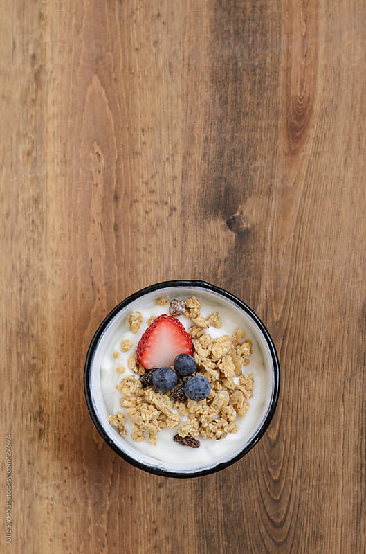 Bowl of yogurt, granola, and fruit on wooden tabltop by Julie Rideout for Stocksy United