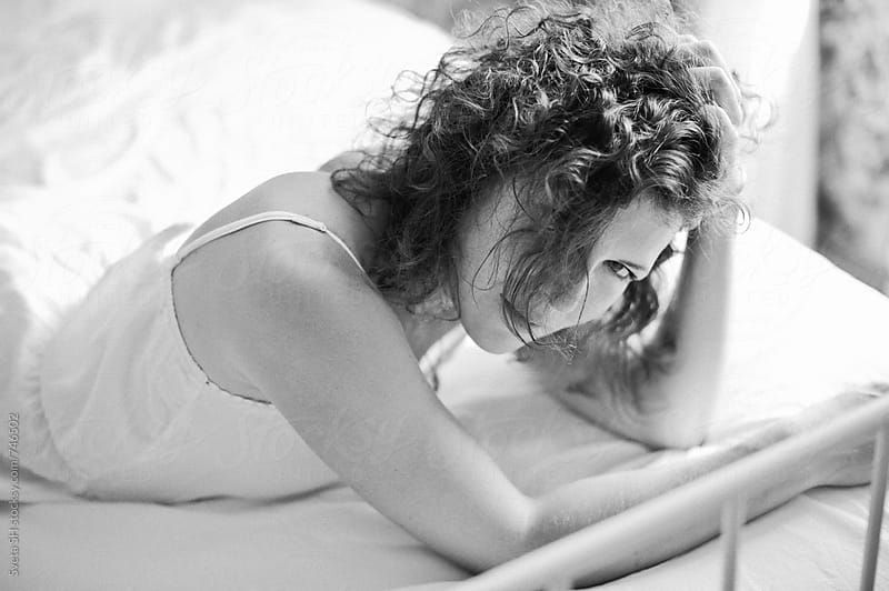 Portrait of young woman in her bedroom by Svetlana Shchemeleva for Stocksy United
