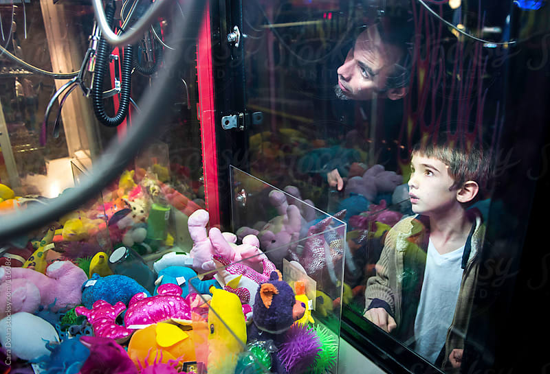 A boy and his father try their hand at a claw crane game at an arcade by Cara Dolan for Stocksy United
