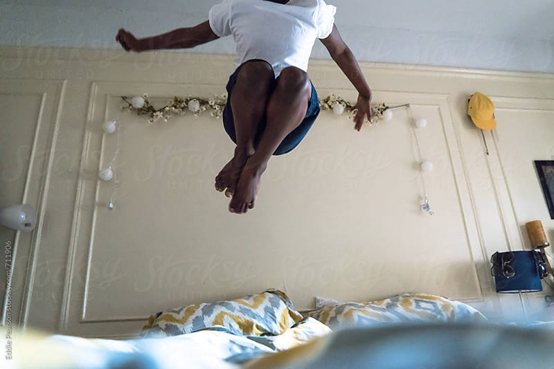 Young boy jumping on his bed by Eddie Pearson for Stocksy United