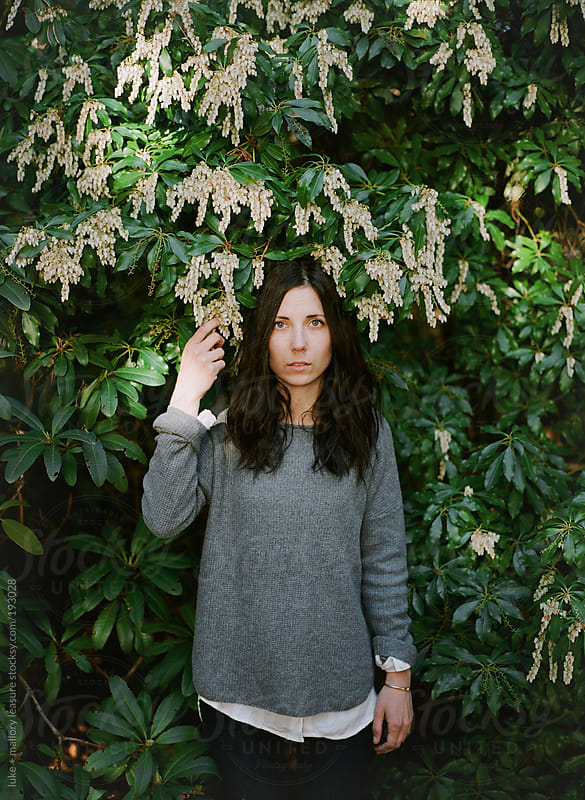 Girl Standing in front of a bush by luke + mallory leasure for Stocksy United