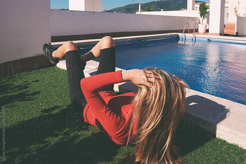 Girl doing abs exercise at pool. by Guille Faingold for Stocksy United