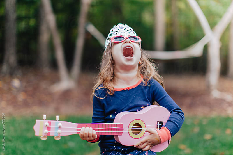 Funny young girl playing a toy guitar and howling by Jakob for Stocksy United