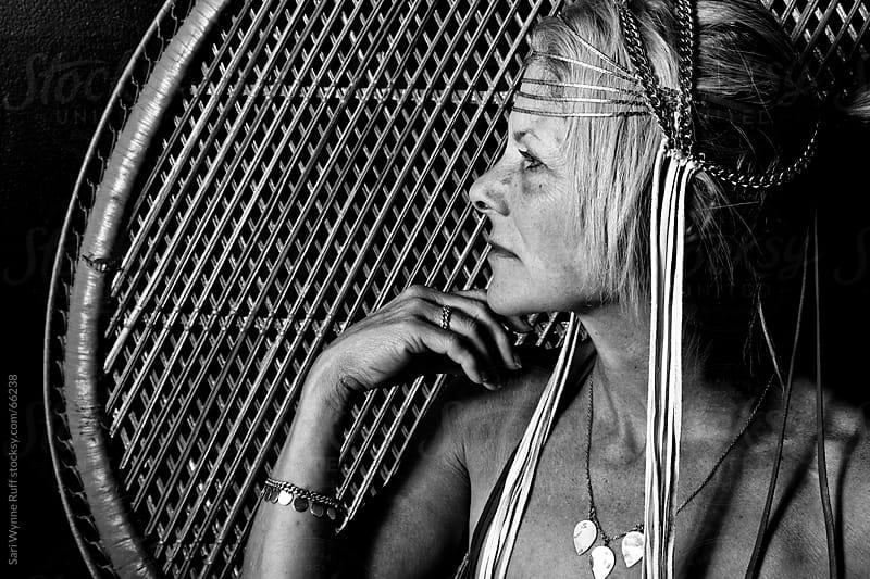 Blonde woman in wicker chair by Sari Wynne Ruff for Stocksy United