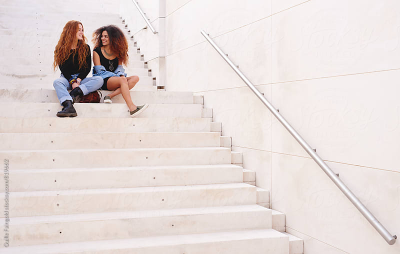 Two girlfriends laughing together while sitting on stairs by Guille Faingold for Stocksy United
