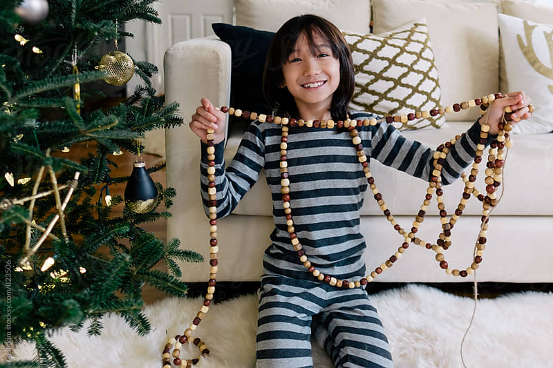 Happy multiracial boy shows wood garland he made by kelli kim for Stocksy United