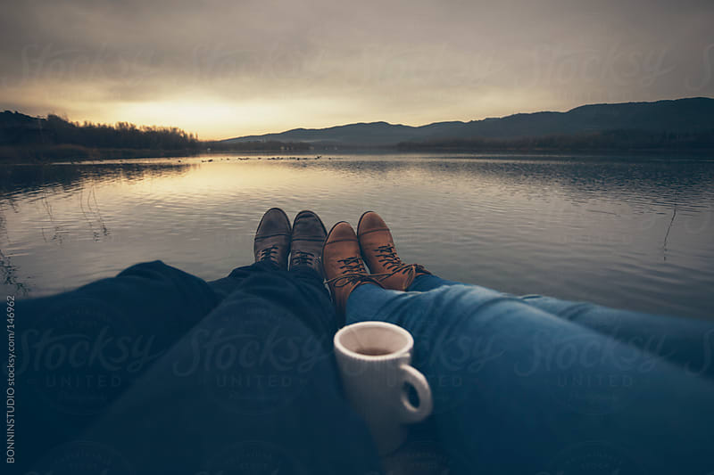 Closeup of legs of couple relaxing at the lakeshore. by BONNINSTUDIO for Stocksy United