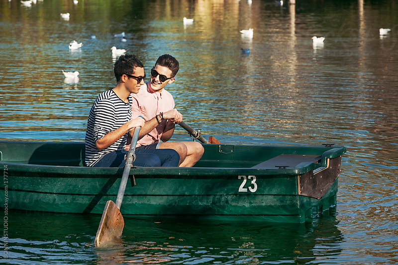 Gay couple rowing boat on a lake. by BONNINSTUDIO for Stocksy United