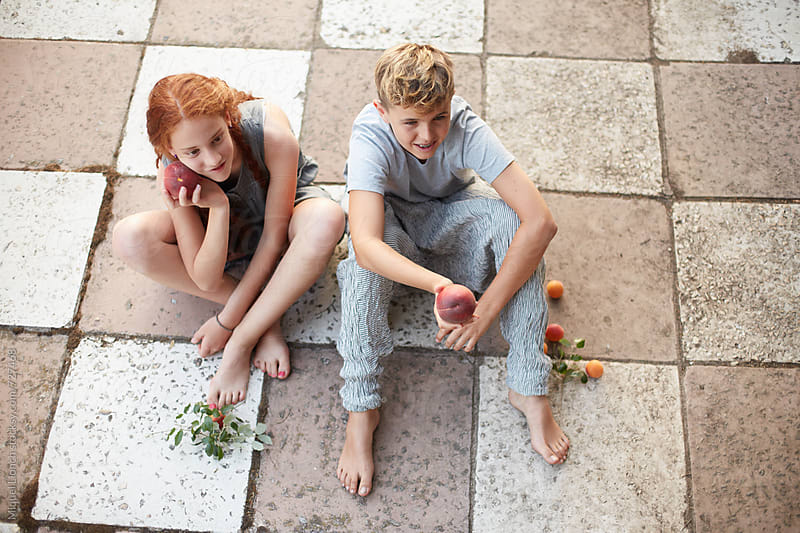 Young couple of teens sitting on the ground with some fruit by Miquel Llonch for Stocksy United
