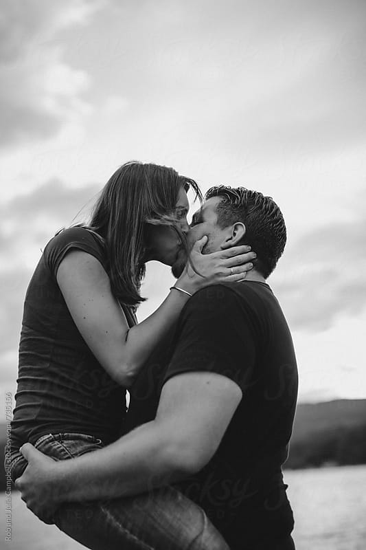 Young couple kissing together at the lake by Rob and Julia Campbell for Stocksy United