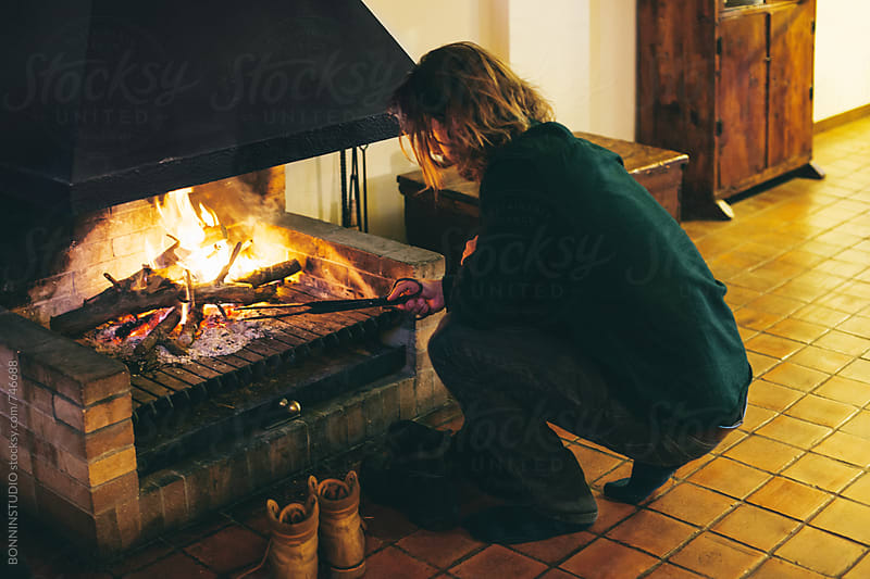 Man in front of a fireplace on winter. by BONNINSTUDIO for Stocksy United