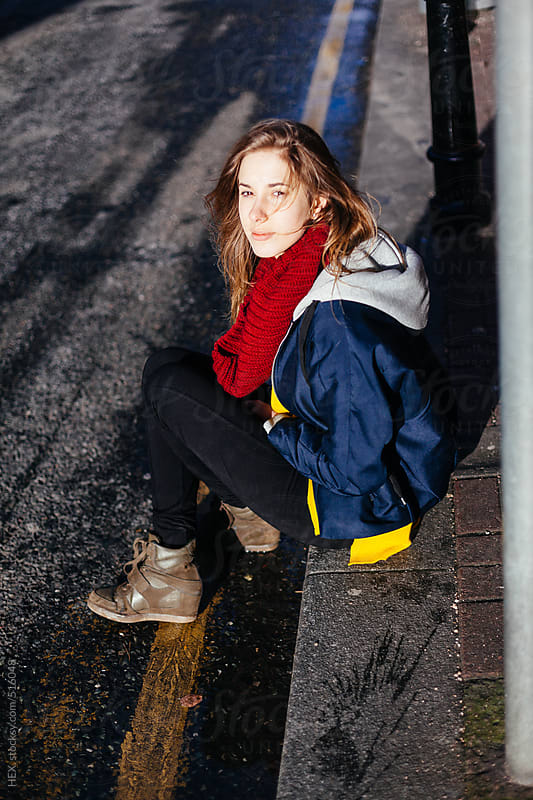 Young Blonde Woman Sitting on the Sidewalk in the City by HEX. for Stocksy United