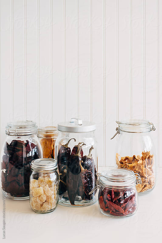 A group of dried fruits and peppers in glass jars on a white countertop. by Lucas Saugen for Stocksy United