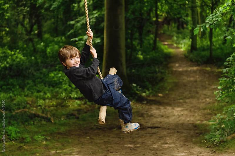 Boy on tree swing by Rebecca Spencer for Stocksy United