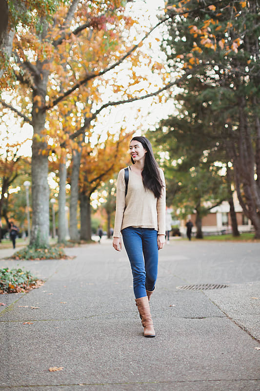 Young mixed race woman - asian & caucasian - walking outside with backpack on fall day by Rob and Julia Campbell for Stocksy United