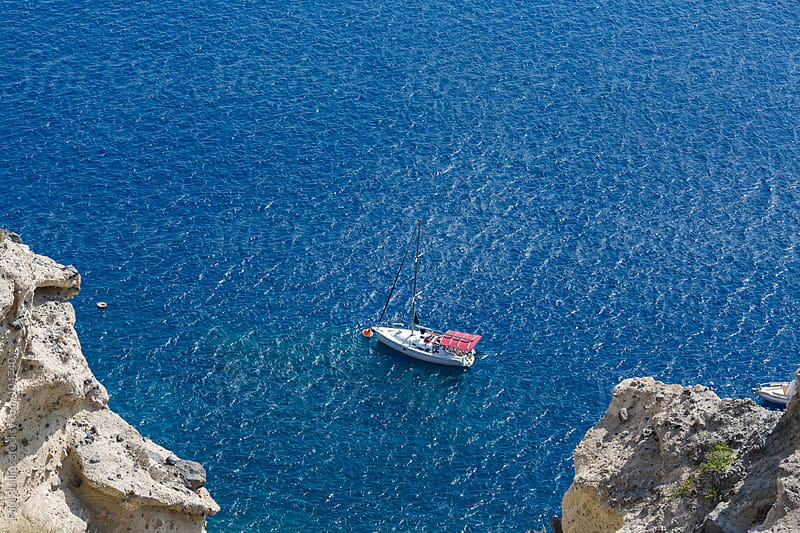 Elevated view of a small sailboat moored in calm blue water by Paul Phillips for Stocksy United