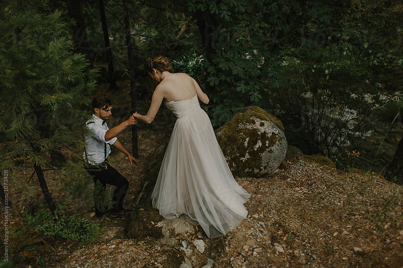 Bride and Groom Walking Through Forest by Sidney Morgan for Stocksy United