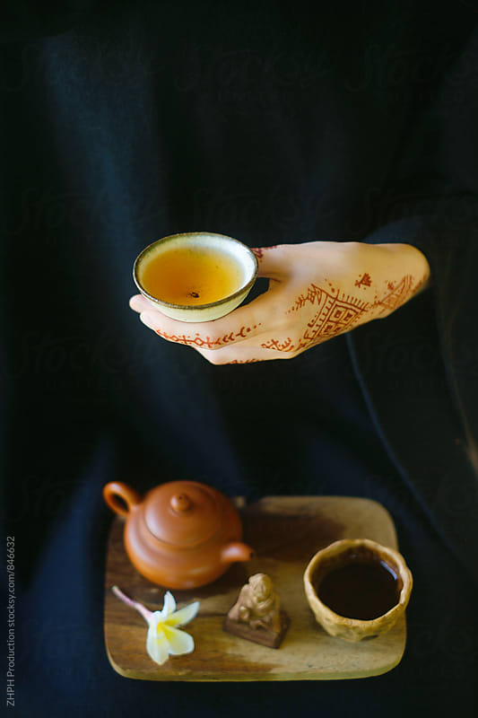 Cup of tea and tattooed hand by Artem Zhushman for Stocksy United