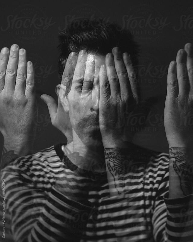 Multiple exposure of a man covering his face with his hands  by Cameron Whitman for Stocksy United