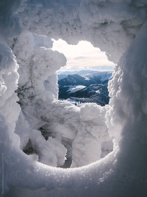 Velka Fatra mountains framed in hole in snow by Martin Matej for Stocksy United