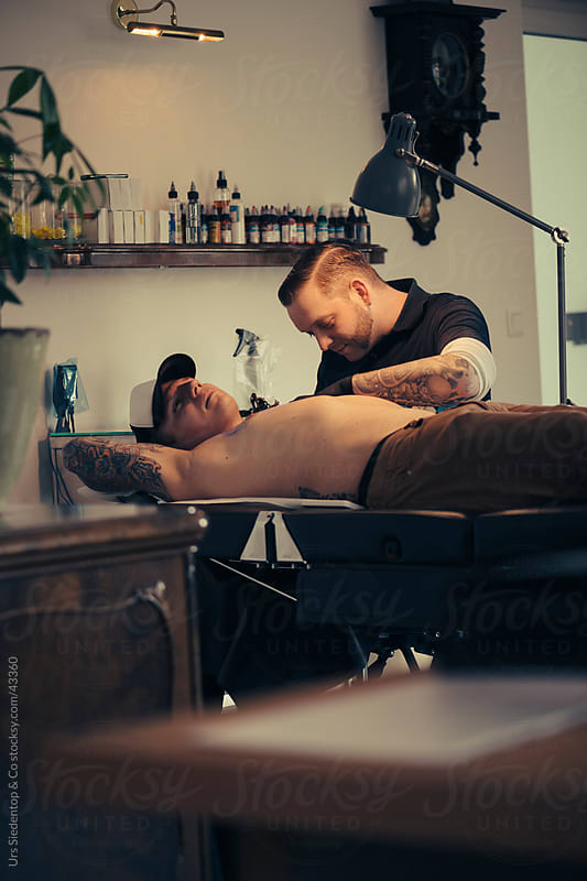 Tattoo artist Rolf Bergmann at work by Urs Siedentop & Co for Stocksy United