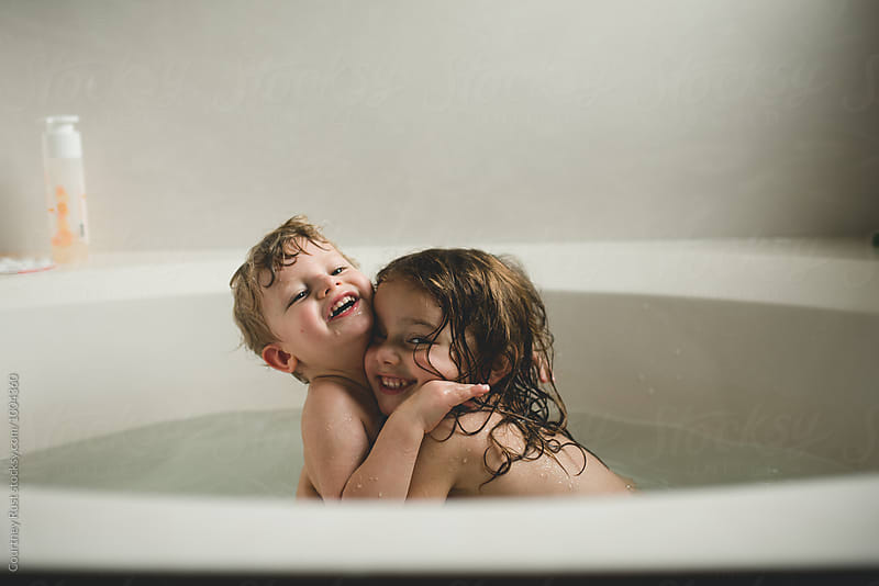 Siblings hugging in bathtub  by Courtney Rust for Stocksy United