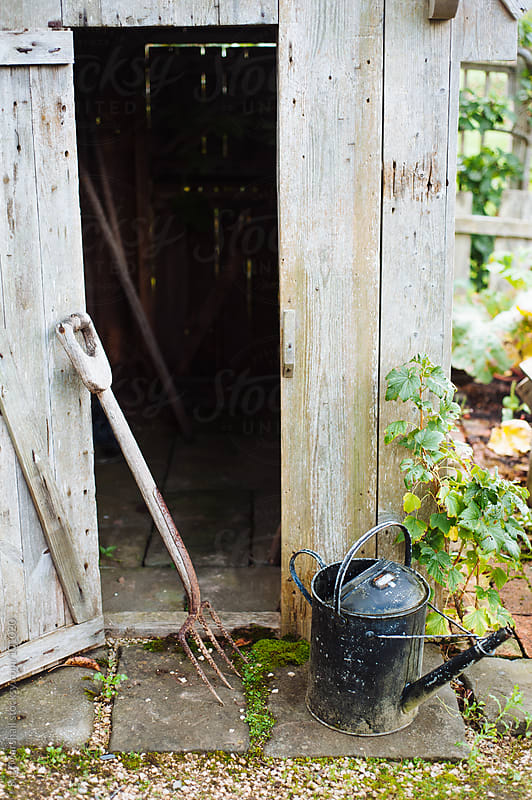 Rusty garden fork and watering can next to a garden shed by Suzi Marshall for Stocksy United