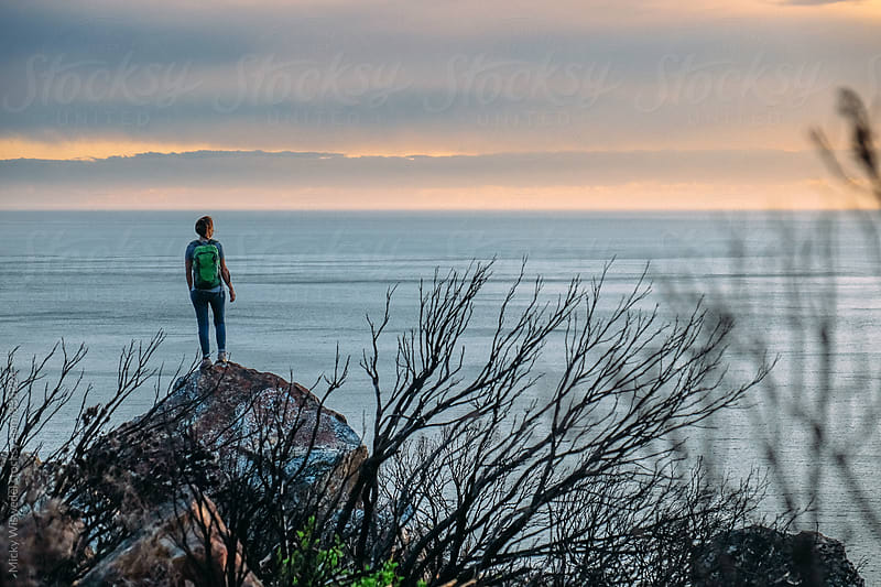Hiker on a rock overlooking the sea at sunset by Micky Wiswedel for Stocksy United