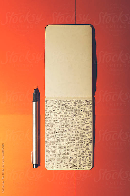 Squared doodle in notebook on orange... by Catherine MacBride for Stocksy United