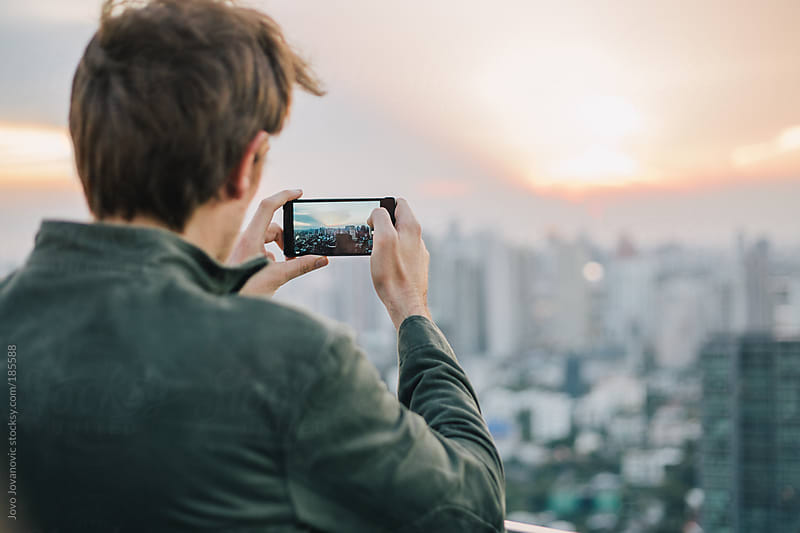 Capturing the amazing view - man taking picture with his smartphone by Jovo Jovanovic for Stocksy United