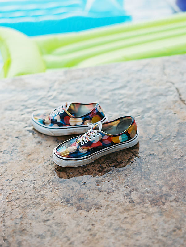 colorful sneakers skate shoes next to pool by wendy laurel for Stocksy United