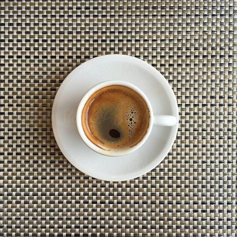 Overhead shot of espresso on a brown patterned placemat. by Holly Clark for Stocksy United