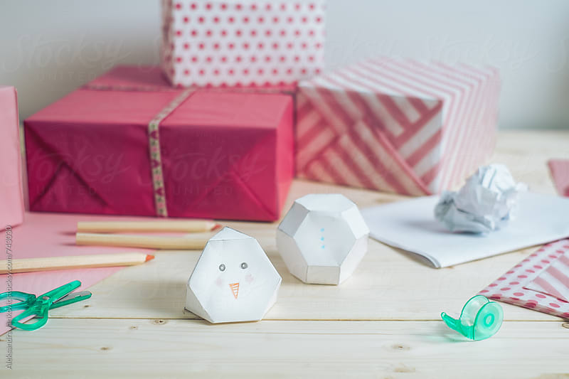 DIY Paper Snowman on the Desk in Front of Pink Presents by Aleksandra Jankovic for Stocksy United