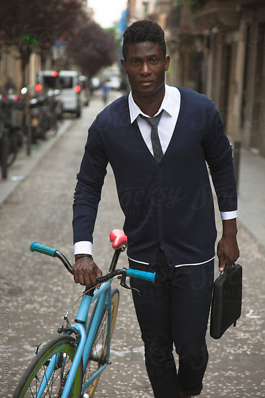 African young man with briefcase and his bicycle by BONNINSTUDIO for Stocksy United