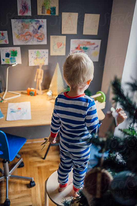Blond Boy Standing on a Chair and Decorating the Christmas Tree by Lumina for Stocksy United