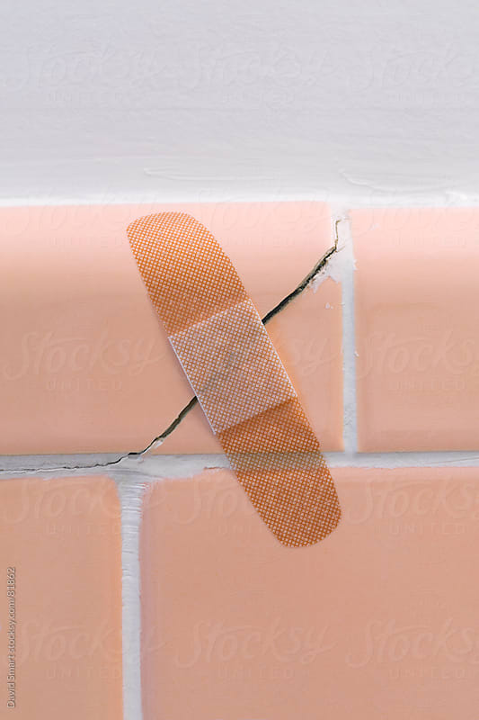 Do it yourself home repair - a bandage on cracked ceramic tile by David Smart for Stocksy United