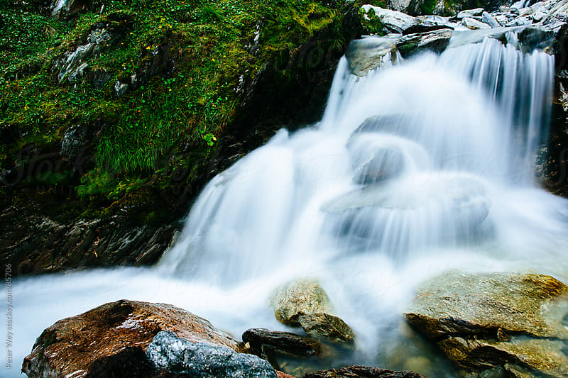 Alpine waterfall in a foggy valley by Peter Wey for Stocksy United