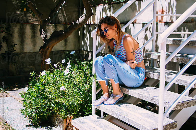 Fashion woman sitting on the stairs of her garden by Susana Ramírez for Stocksy United