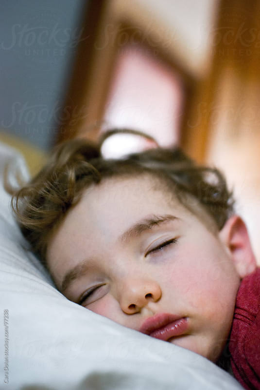 Toddler boy sleeping in the afternoon with his face squished into the pillow by Cara Dolan for Stocksy United