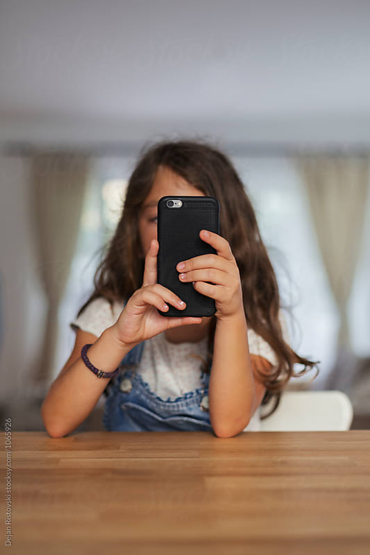 Child playing games on mobile phone. by Dejan Ristovski for Stocksy United