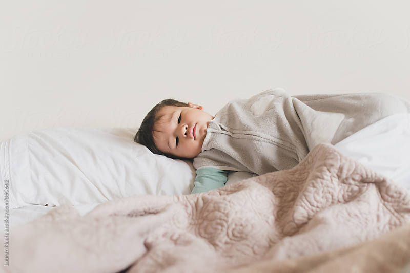 Baby lying on pillow by Lauren Naefe for Stocksy United