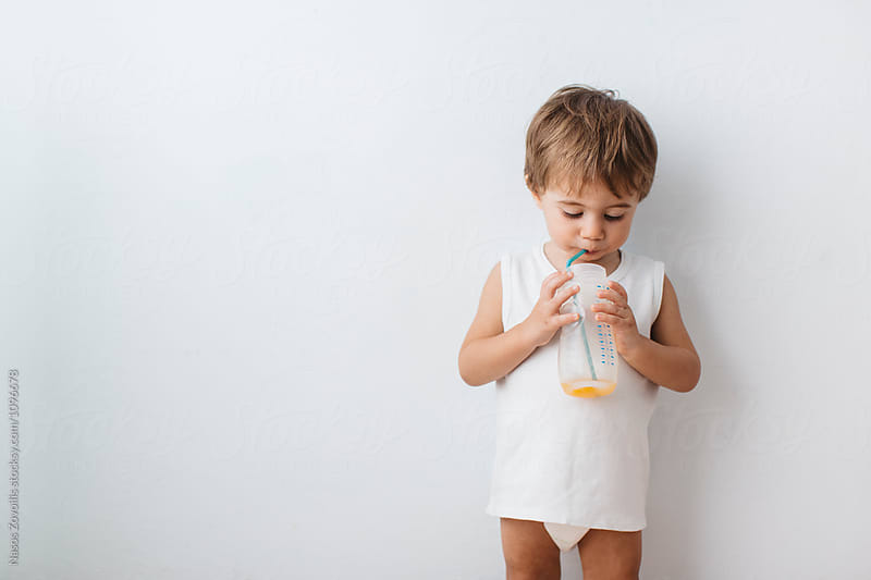 1 year old boy drinking orange juice by Nasos Zovoilis for Stocksy United
