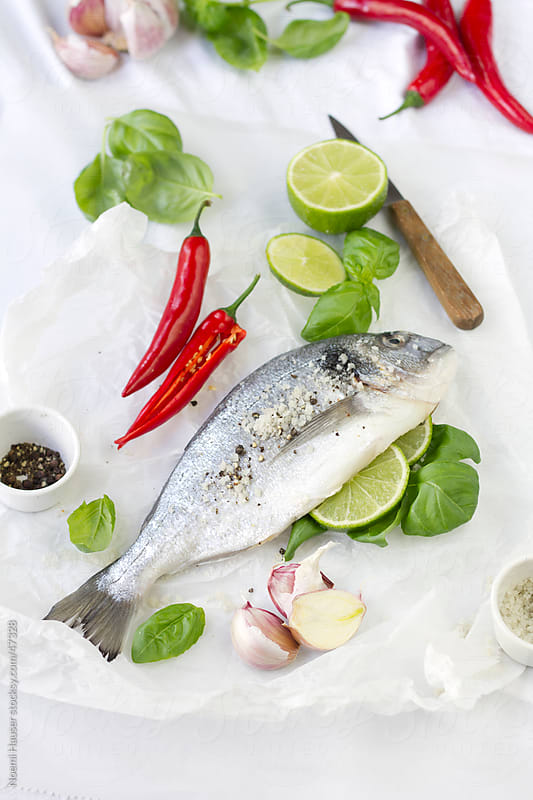 Gilthead seabream with lime, garlic, basil and chili by Noemi Hauser for Stocksy United