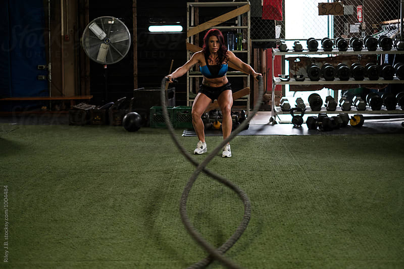 Muscular woman using battling ropes by Riley Joseph for Stocksy United