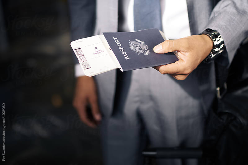Closeup of a hand holding passport and boarding pass by Per Swantesson for Stocksy United