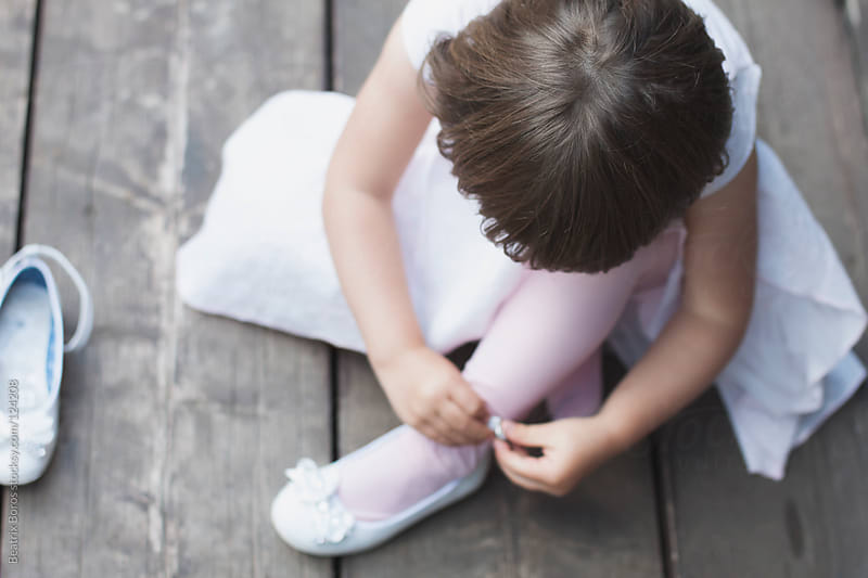 Little ballerina tying her shoes by Beatrix Boros for Stocksy United