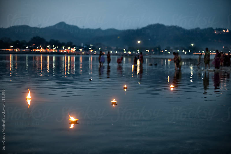 Candles on the River Ganges. The sacred river of India where pilgrims come during the kumbh Mela by Jean-Claude Manfredi for Stocksy United