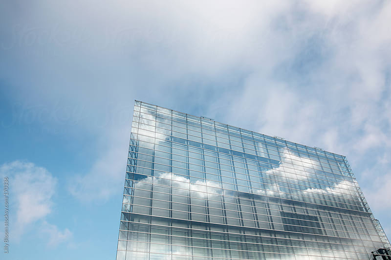 Clouds mirroring in the facade of an office building by Lilly Bloom for Stocksy United