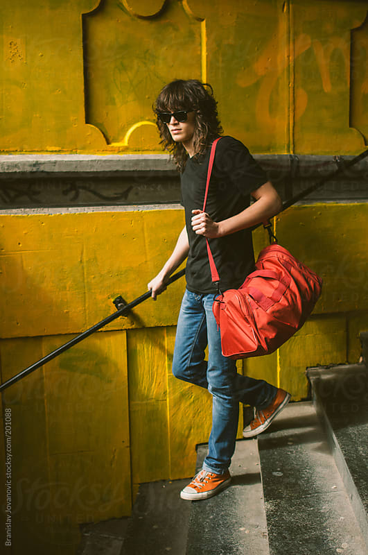 Young man with red traveling bag going down the stairs by Branislav Jovanovic for Stocksy United